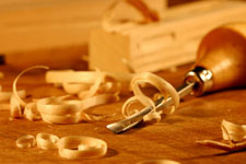 chisel lying beside pieces of wood and wood shavings